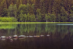 Peaceful lake scenery. Peaceful scenery with mountain lake with rocks and forest reflections into the calm, translucent waters, Saint Ana (Sfanta Ana) lake Royalty Free Stock Photos