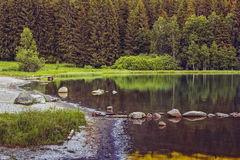 Peaceful lake scenery. Peaceful scenery with the shore and calm translucent waters of the Saint Ana (Sfanta Ana) lake, Romania Royalty Free Stock Photo