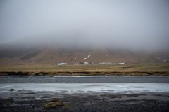 Fog cloud coming down a valley in Iceland, a line of small houses. Peaceful landscape in Iceland, dusk, river flows, a line of houses along the mountain Royalty Free Stock Photo