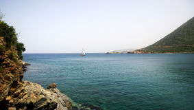 Peaceful landscape - sea, rocks and a yacht in the distance swam into the Bay Stock Photos