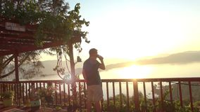 Man Watching Sunrise while drinking Coffee stock video footage