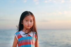 Peaceful little child girl standing on beach at sunset light with looking camera stock image