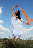 Peaceful looking woman. Woman peacefully standing in the wind holding orange sarong Stock Images