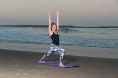 Peaceful lunge stretch near breaking waves of Pacific Ocean. Crescent Moon Yoga pose in pattern tights along coastline stock images