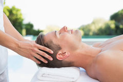 Peaceful man getting a head massage poolside Royalty Free Stock Photos