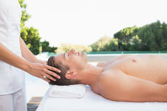 Peaceful man getting a head massage poolside Royalty Free Stock Image