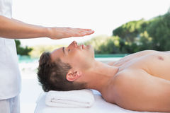 Peaceful man getting reiki treatment poolside Stock Photo