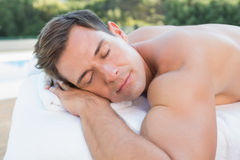 Peaceful man lying on massage table poolside Royalty Free Stock Photo