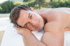 Peaceful man lying on massage table poolside Royalty Free Stock Photography