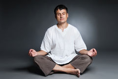 Peaceful man meditating isolated over dark Royalty Free Stock Images