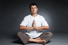 Peaceful man meditating isolated over dark Stock Images