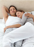 Peaceful man thinking while relaxing. With his girlfriend in the bedroom Stock Image