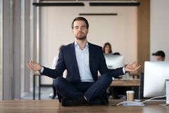 Peaceful businessman meditating with eyes closed at workplace royalty free stock photo