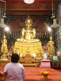 Peaceful mind. A white-dressed woman sitting for meditation and praying peacefully in front of golden Buddha statue in Wat Pak Nam, a Buddhist temple, in Bangkok Royalty Free Stock Photography