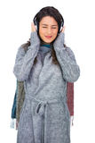 Peaceful model wearing winter clothes listening to music Royalty Free Stock Photos