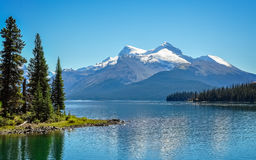 Peaceful morning at Lake Maligne. Maligne Lake is the largest glacially fed lake in the Canadian Rockies.  It is famed for the beautiful blue colour of its water Stock Image
