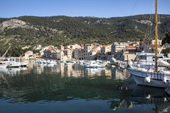Peaceful morning in little harbour. Fisherman`s boats and old stone houses in port of Komiza on island Vis in Croatia royalty free stock images