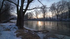 Calm morning with sunrise over trees on the river bank Dolly shot. Peaceful morning with sunrise on the bank of the river with trees and sun-beams mirroring in stock footage