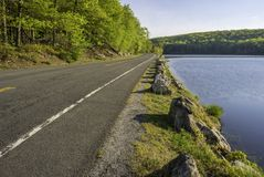 Forest road at Harriman, New York. Peaceful morning view featuring road passing through the trees and lake at Seven lakes road, New York royalty free stock images