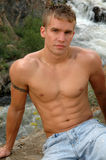 Peaceful Mountain. A handsome muscular man sitting above a mountain river Royalty Free Stock Photo