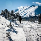 Mountain in snow, man walking stock images