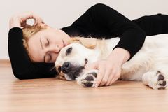 Peaceful Nap, Young woman and her dog. Are napping on the floor. She is hugging her Golden Retriever. Her dog seems like he is on guard duty or just woke up royalty free stock photography