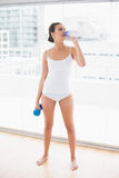 Peaceful natural brown haired woman in white sportswear drinking water while holding a dumbbell Stock Photography
