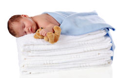 Peaceful Newborn. A newborn baby boy holding a small teddy bear while sleeping soundly on a pile of fluffy white towels.  Isolated on white Royalty Free Stock Image