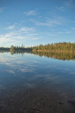 Peaceful Northern Ontario lake in early morning with reflected c Royalty Free Stock Photography