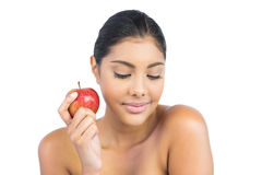 Peaceful nude brunette holding red apple Royalty Free Stock Image