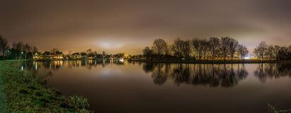Peaceful panoramic view of river and trees backlit by Amsterdam city lights Stock Image