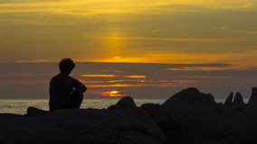 Peaceful. A person sitting peacefully on a rocky shore at sunset Stock Image