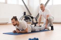 Peaceful physical therapist stretching the disabled patient in the gym Stock Photo