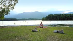 Peaceful picture girl sits in lotus pose on calm lake bank. Peaceful picture girl sits in lotus pose by small rocks on calm lake bank under sunset sky stock footage
