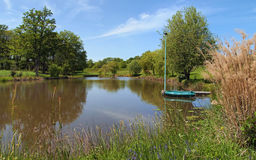 Peaceful pond with small boat Stock Images