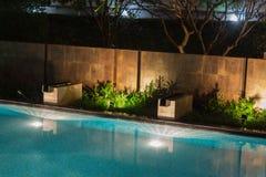 Peaceful pool reflections amid mood lighting and lush greenery g Stock Photos