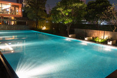 Peaceful pool reflections in the evening twilight with warm still water filled to the brim and ready for swimming. Bright mood l. Ighting casting glare into the royalty free stock photo