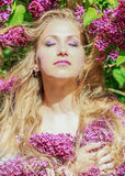 Peaceful portrait. Of a beautiful young woman among the lilac flowers ,sunshine on the face Stock Image
