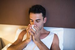 Peaceful portrait of handsome young man drinking cup of coffee i. N the white bed Royalty Free Stock Photography