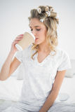 Peaceful pretty blonde wearing hair curlers drinking coffee Stock Photos