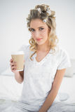 Peaceful pretty blonde wearing hair curlers holding coffee Royalty Free Stock Photo