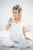 Peaceful pretty blonde wearing hair curlers smelling coffee Royalty Free Stock Photography