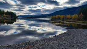 Peaceful and quiet untouched landscape scenery of pebble beach and lake with dramatic clouds reflected in the calm water. With autumn trees around and rural royalty free stock image
