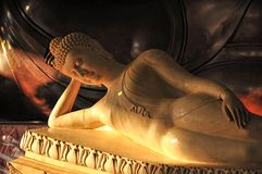 Peaceful reclining marble Buddha statue. Light on peaceful reclining Buddha statue Royalty Free Stock Photography