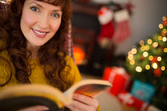 Peaceful redhead reading a book at christmas Stock Photography