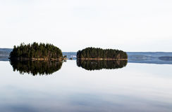 Peaceful reflections of sister islands. This is a picture from the largest Lake in Halden, Norway.. To see the lake as quiet as this is very rare and a one in a Stock Image