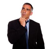 Peaceful and reflective man touching the chin. Portrait of a peaceful and reflective man touching the chin while thinking on black suit on isolated background Stock Images