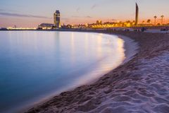 Peaceful and relaxing view of barcelona beach during purple warm summer sunset with long exposure of sea. And relaxing view of barcelona beach during purple warm stock photo