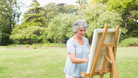 Peaceful retired woman painting on canvas Royalty Free Stock Photos