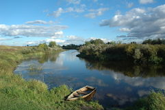 Peaceful River. Tranquil, relaxing panorama from the bank of a quiet Russian river with a row boat partially submerged in the foreground and beautiful clouds in royalty free stock photography